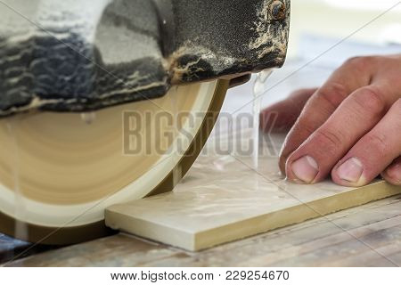 Worker Hand Cutting Ceramic Tile With Water Cutting Machine Close-up.