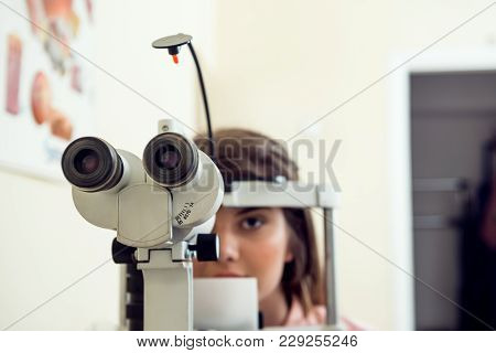 Portrait Of Cute Caucasian Female Patient Sitting In Optometrist Office, Waiting For Start Of Proced