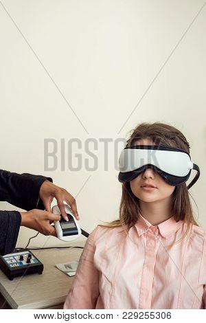 Horizontal Portrait Of Cute European Female Patient Sitting In Eye Specialist Office, Wearing Digita