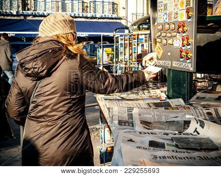 Lisbon, Portugal - Feb 10, 2018: Woman Receiving Change At Press Kiosk After Buying Fresh Newspaper