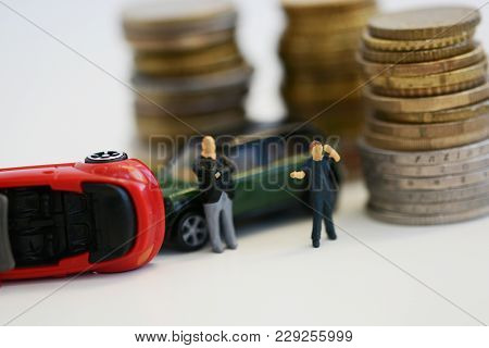 Miniature People And Toy Cars Involved In An Accident In Front Of Piles Of Money, Suggesting Vehicle