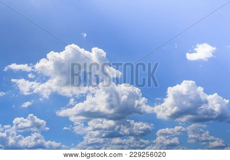 Blue Sky With Puffy White Clouds In Bright  Sunny Day