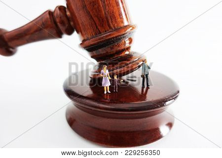 Divorce And Child Custody Concept With Family Figurine On Wooden Judge Gavel