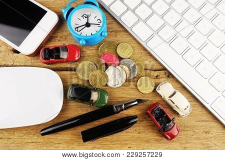 Online Car Insurance With Miniature Car Toys, Money, Alarm Clock And Computer Keyboard On Wooden Tab