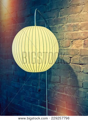 Lamp With Round Lampshade On Brick Wall. Retro Style Image With Light Leaks.