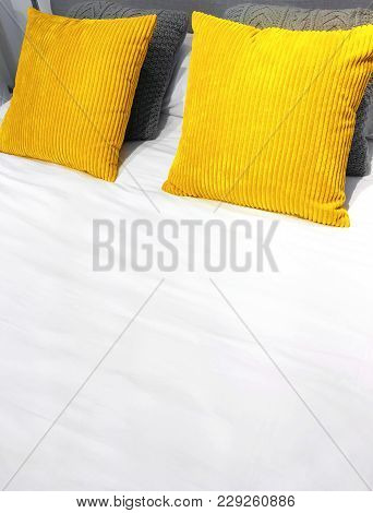 Bed With Bright Yellow Velveteen Cushions And White Bed Sheets.