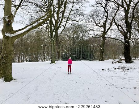 """HAMPSTEAD, LONDON - MARCH 1, 2018: A female jogger runs on Hampstead Heath during Storm Emma, also known as the """"Beast from the East"""" weather front, in Hampstead, North London, UK."""
