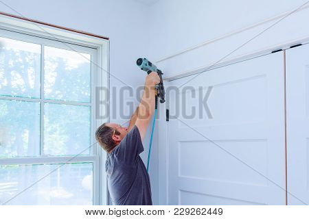 Carpenter Brad Using Nail Gun To Moldings On Doors, Framing Trim, With The Warning Label That All Po