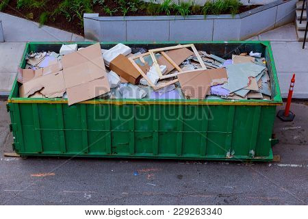 Construction Waste In An Metal Container, Home House Renovation. Container For Construction Waste