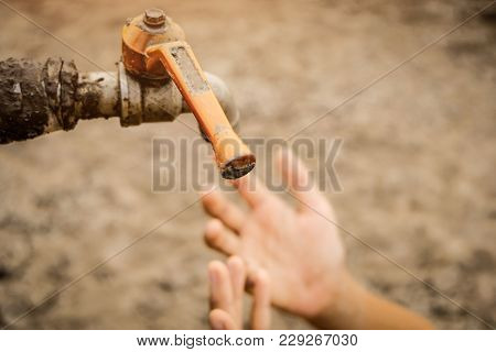 Sad Kids Sitting On Cracked Earth Open Metal Water Old Faucet On Hot And Dry Empty Land. Affected Of