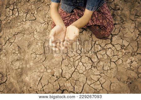 Sad Kid Despair Sitting On Cracked Earth On Hot And Dry Empty Land. Affected Of Global Warming Made
