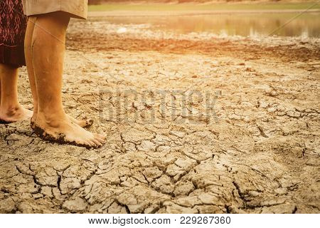 Barefoot On Land With Dry And Cracked Ground.  Affected Of Global Warming Made Climate Change. Water