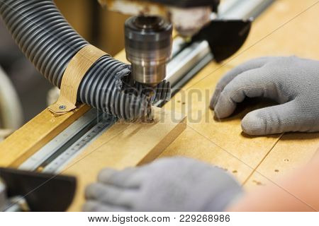 production, manufacture and woodworking industry concept - hands of carpenter working with drill press and board at workshop