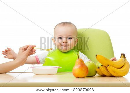 Baby Having A Table Full Of Healthy Food. Cheerful Toddler With Fruits Apples, Bananas, Pear. Mother