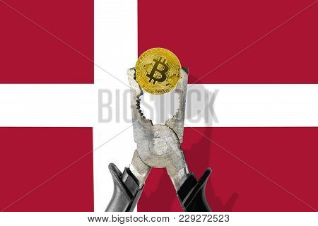 Bitcoin Coin Being Squeezed In Vice On The Denmark Flag Background; Concept Of Cryptocurrency Bitcoi