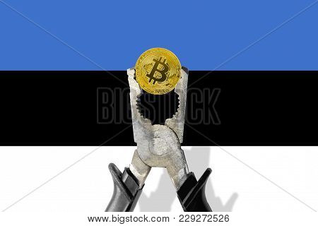 Bitcoin Coin Being Squeezed In Vice On The Estonia Flag Background; Concept Of Cryptocurrency Bitcoi