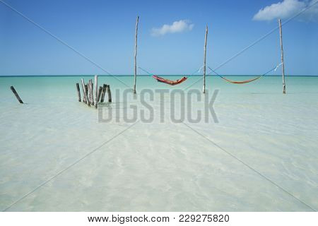 Hammocks hanging over crystal clear water, paradisiacal Caribe
