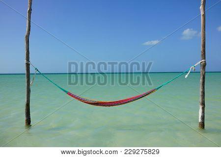 Hammock hanging over crystal clear sea of Caribe