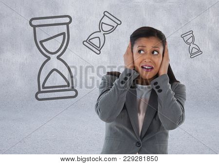 Digital composite of frustrated woman with hourglasses