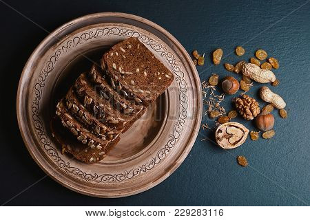 Dark Cereal Bread With Sunflower Seeds, On A Plate, Scalded Nuts On A Dark Background Shale Board, C