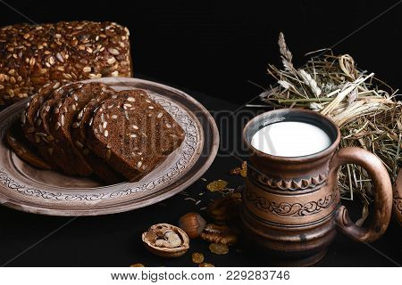 Dark Cereal Bread With Sunflower Seeds, On A Plate, Scalded Nuts, Cup Of Milk On Shale Board, Concep