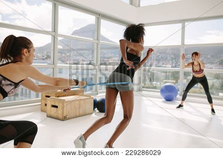 Woman Working Out At Gym With Personal Trainers