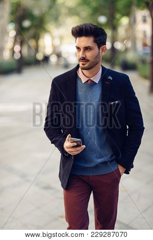 Man In The Street In Formalwear With Smartphone In His Hand.