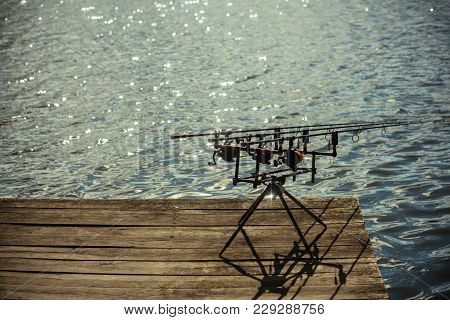 Rods And Reels At River Or Lake Water. Spinning Tackles On Pod On Wooden Pier. Spin Fishing, Angling