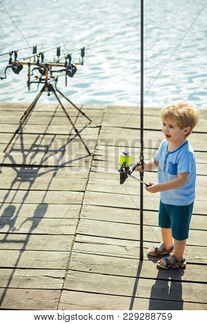 Child With Fishing Rod On Wooden Pier. Little Boy Learn To Catch Fish In Lake Or River. Fishing, Ang