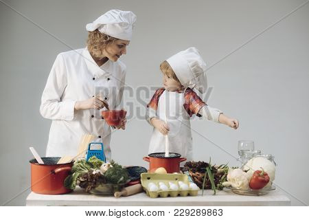 Mother Teaches Son To Cook On Light Background. Mom And Kid With Busy Face Cooking Food Together. Pa