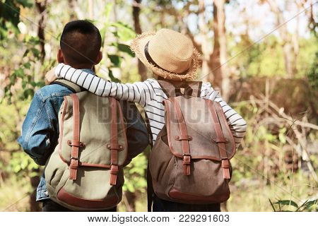 Two Kids Hiking With Backpacks Walking Studying The Route Map In A Sunny Summer Day On A Forest, Rel
