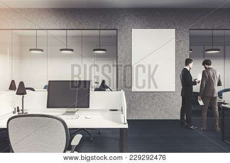 Computer On An Office Cubicle Desk. Gray And Glass Walls With A Large Vertical Poster. A Dark Floor.
