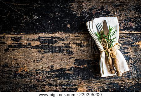 Table Setting With Fresh Rosemary And Rustic Silverware On Dark Wooden Table