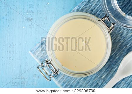 Jar With Condensed Milk Or Evaporated Milk On Blue Table Top View.