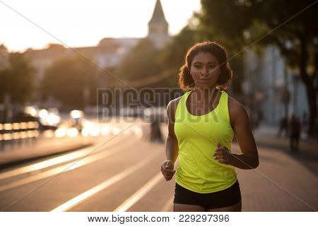Young Fitness Woman Jogging Down The Street