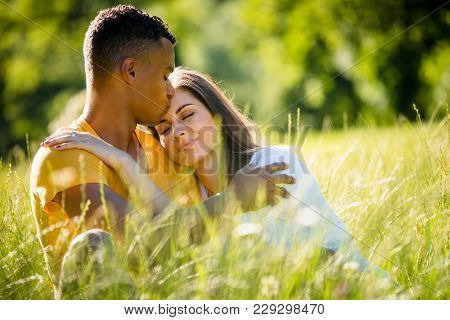 Young Couple Hugging Outdoor In Nature - Woman With Closed Eyes Rest On His Shoulder