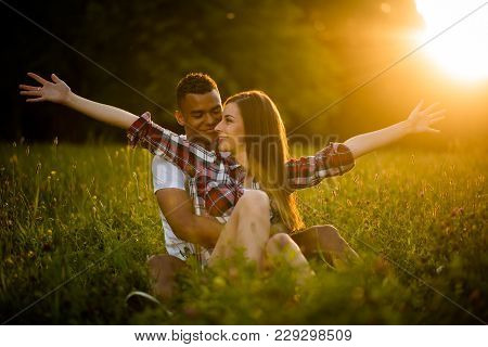 Multi Ethnic Couple Enjoying Being Together In Nature At Sunset - Sitting In Grassfield