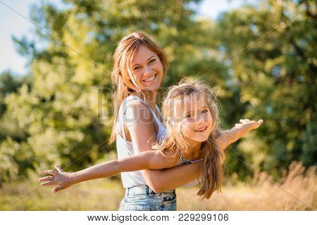 Cute Little Girl Enjoying Airplane Ride In Arms Of Her Elder Sister.