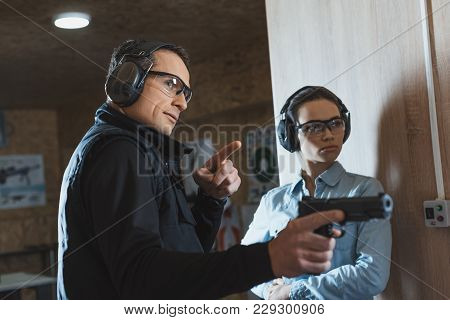 Male Instructor Pointing On Something In Shooting Gallery