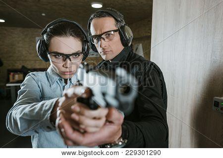 Instructor Helping Customer Holding Gun In Shooting Gallery