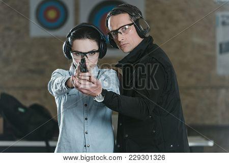 Female Customer Aiming Gun At Camera In Shooting Gallery