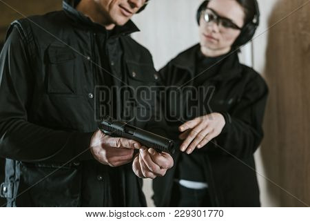 Cropped Image Of Instructor Showing Gun To Female Client In Shooting Gallery