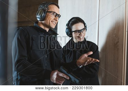 Smiling Shooting Instructor And Customer In Shooting Gallery