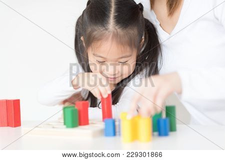 Little Girl Playing Blocks With Mother. Educational Toys For Preschool And Kindergarten Child. Littl