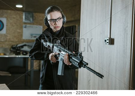 Attractive Girl With Safety Glasses And Headphones Holding Rifle