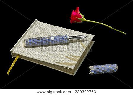 Notepad With Pen And Red Rose On Black Background