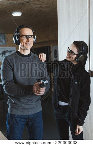 Smiling Shooting Instructor Supporting Client In Shooting Range