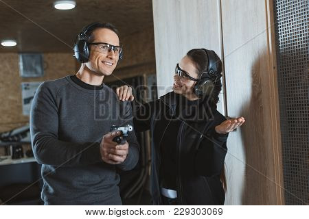 Smiling Shooting Instructor Supporting Client In Shooting Gallery