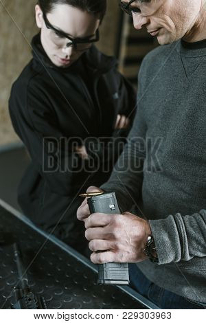 Cropped Image Of Instructor Showing Rifle Magazine To Client In Shooting Gallery