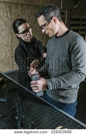 Instructor Showing Rifle Magazine To Client In Shooting Gallery